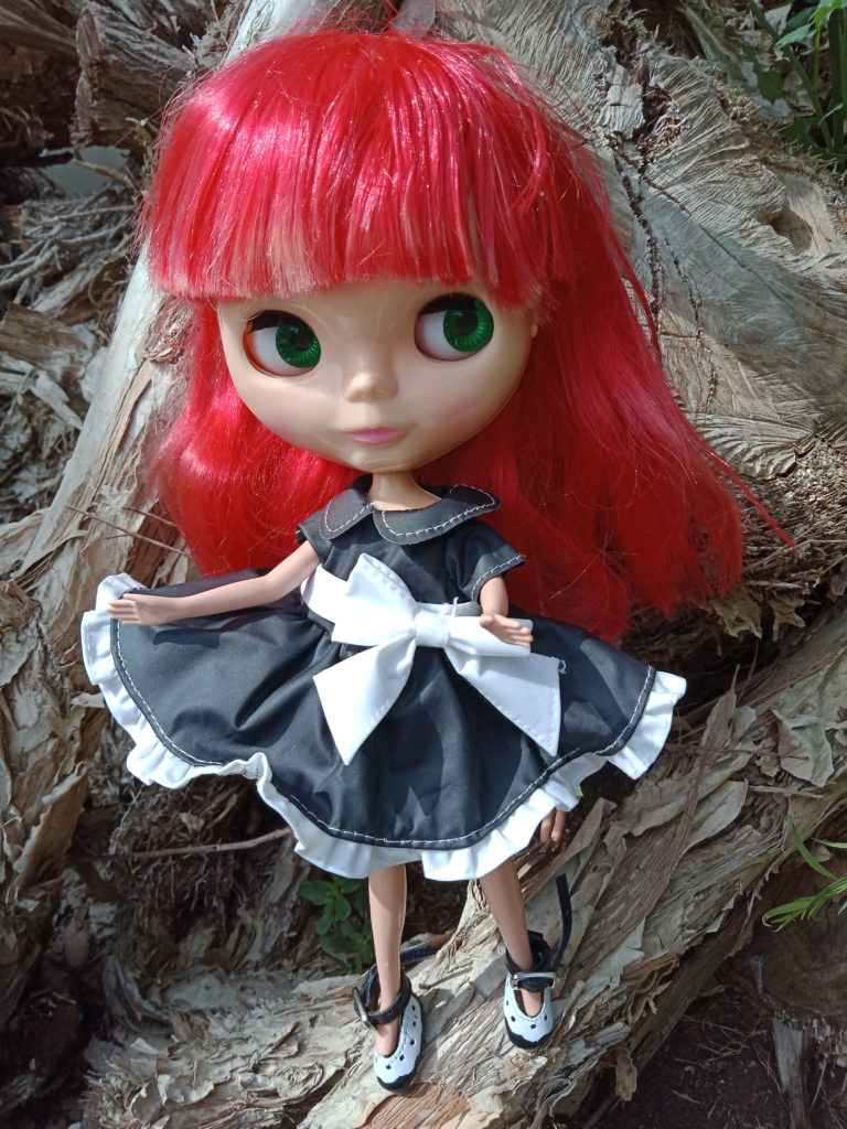 Blythe Doll with red hair black dress with a whit bow